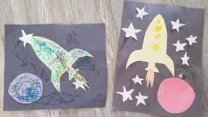 construction paper rocket ship craft with circular coloured planet and rocket ship on black paper with aluminum foil stars