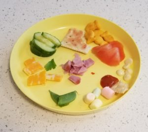 plate with small portion of different healthy foods for mystery food game tasting