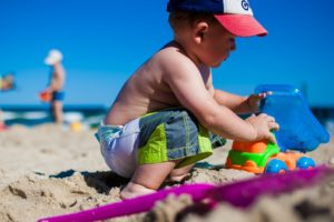 toddler boy playing at beach in summer