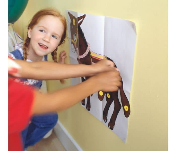 Girl Playing Pin the Tail on the Donkey