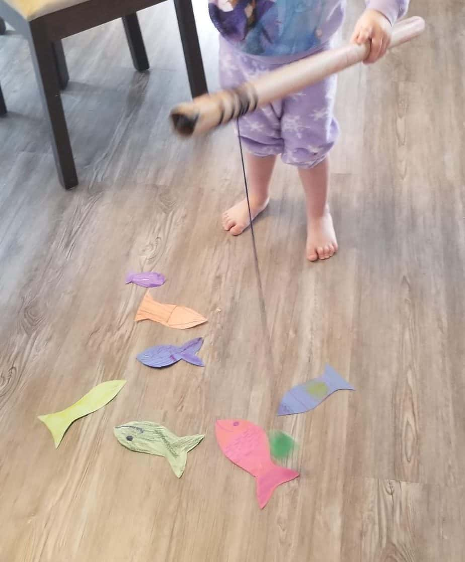 child catching a fish with the toddler fishing game